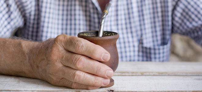 Eine Männerhand umfasst eine Kalebasse, das runde Trinkgefäß für Mate Tee.