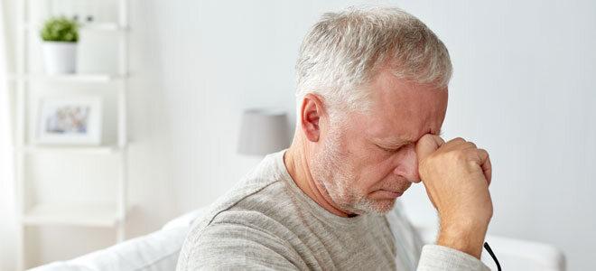 Ein Mann hat Cluster-Kopfschmerzen, sie fühlen sich wie starke, stechende Schmerzen hinter dem Auge an.