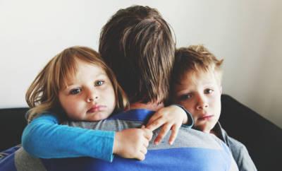 EIn Vater umarmt seinen Kinder, eine Tochter und einen Sohn.