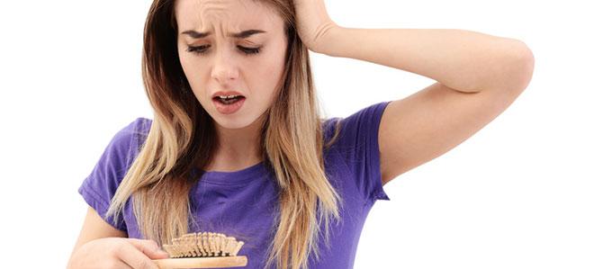Eine Frau schaut erschrocken auf ihre Haarbürste, in der sich viele ausgefallene Haare befinden. Haarausfall ist ein Symptom von Hirsutismus.