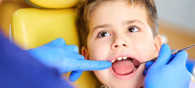 Ein Schuljunge wird zahnärztlich behandelt. Der Zahnarzt überprüft, ob das Kind Kreidezähne (MIH) hat.
