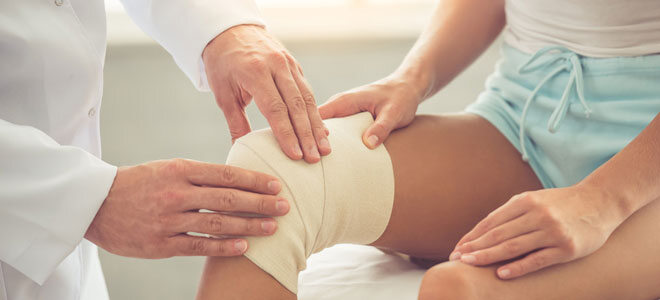Ein Arzt bandagiert das rechte Knie einer jungen Patientin.