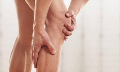 Ein Mann hält seine Hände über sein rechtes schmerzendes Knie.