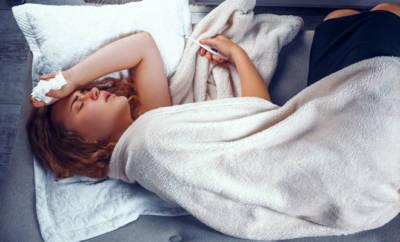 Eine junge Frau liegt mit Fieber auf dem Sofa.