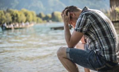 Ein Mann mittleren Alters sitzt traurig an einem Seeufer. Er leidet an einer
