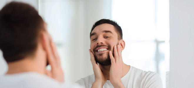 Ein junger Mann blickt selbstverliebt in den Spiegel und berührt mit den Händen seine Wangen.