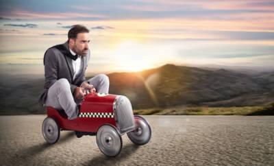 Ein Mann im Anzug rollt in einem Kinderspielauto eine asphaltierte Straße entlang.