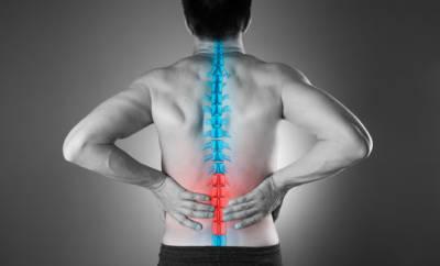 Ein Mann hat Schmerzen an der Wirbelsäule. Der Grund ist die Nervenkrankheit Myelitis, bei der Teile des Rückenmarks entzündet sind.