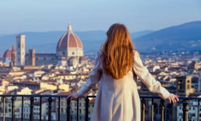 Eine junge rothaarige Frau überblickt die Altstadt von Florenz von einer Dachterrasse aus.