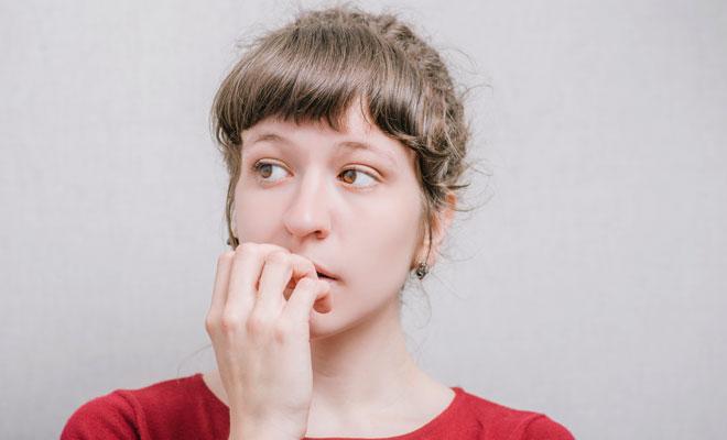 Eine junge brünette Frau kaut nervös an ihren Fingernägeln.