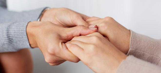 Eine Frau hält die Hände einer Freundin, die in Trauer ist.