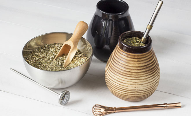 Zubehör für das Trinken von Mate Tee: Getrocknete Yerba Mate Blätter, ein Kalebasse Trinkgefäß, ein Bombilla Strohalm und ein Thermometer.