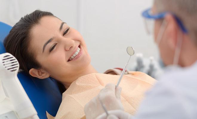 Eine junge Patientin blickt ihren Zahnarzt fröhlich und angstfrei an.