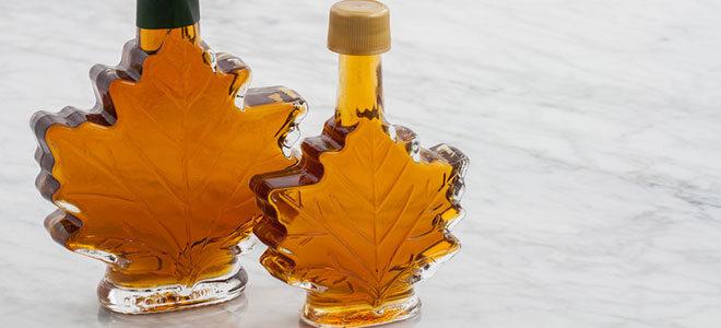 Zwei dekorative Fläschchen in Ahornblattform, die mit Ahornsirup gefüllt sind.