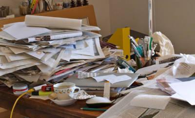 Messie-Syndrom: Ein mit diversen Gegenständen überhäufter, kaum noch nutzbarer Schreibtisch.