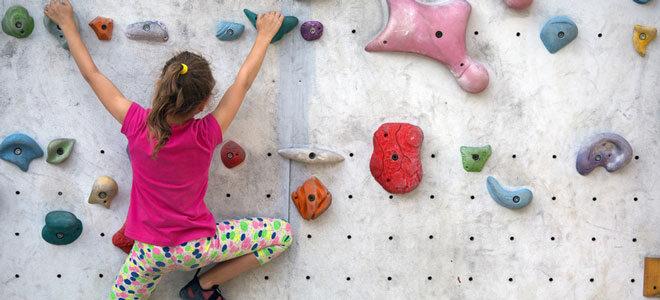 Ein Schulmädchen klettert freihändig an einer Boulderwand entlang.