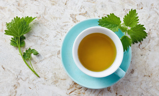 Eine Tasse mit frisch aufgebrühtem Brennnesseltee. Er gilt als natürliches Mittel für mehr sexuelle Lust.