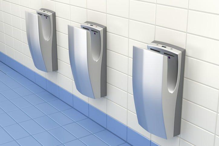Drei elektrische Drucklufthandtrockner in einer öffentlichen Toilette.