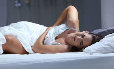 Eine Frau mit Bauchschmerzen, ausgelöst durch Favismus