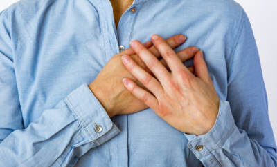 Eine Frau in den Wechseljahren hat Brustschmerzen und bedeckt ihre rechte schmerzende Brust mit den Händen.
