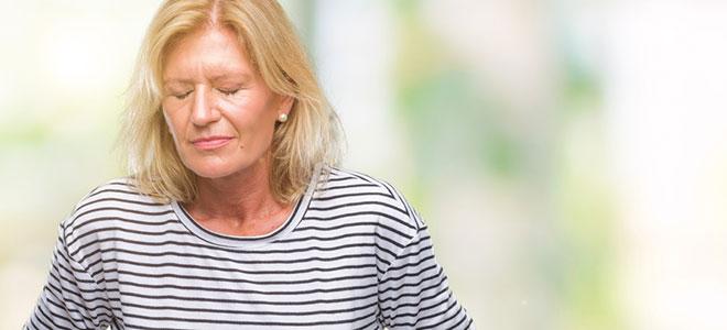 Eine Frau mittleren Alters schaut angestrengt aus.