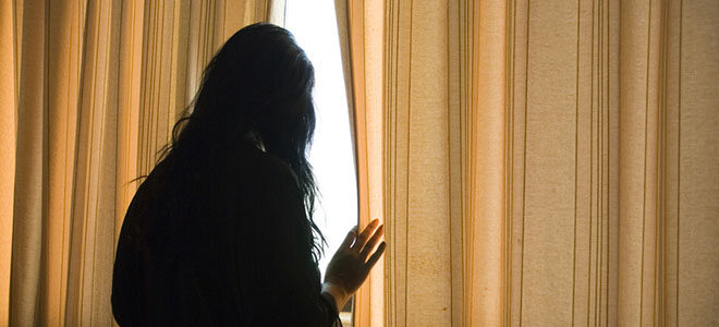 Eine Frau blickt aus dem Fenster.