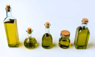 Fünf Flaschen mit verschiedenen gesunden Ölen.