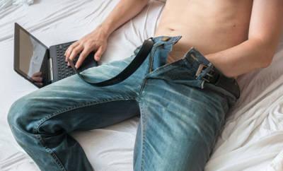 Ein Mann sitzt auf dem Bett und hat seine linke Hand in die Hose gesteckt. Er ist pornosüchtig und masturbiert vor seinem Laptop.