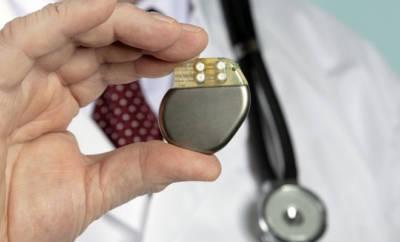 Ein Arzt hält einen Herzschrittmacher in der Hand.