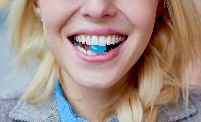 Eine blonde Frau hält einen blauen Hustenbonbon zwischen ihren Zähnen.