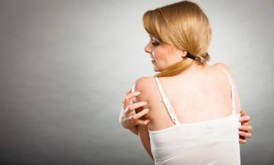 Eine junge Frau leidet an der Skin-Picking-Disorder und hat den ständigen Drang, an unreinen Hautstellen zu kratzen.