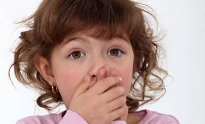Ein junges Mädchen hält die Hand vor den Mund, sie leidet unter Kreidezähnen.