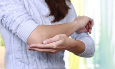 Eine Frau mit dem Muckle-Wells-Syndrom: Sie hat Schmerzen im Ellbogengelenk. Gelenkschmerzen sind ein typisches Symptom dieser Erkrankung.