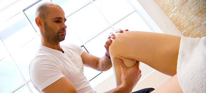 Ein Rolfing-Therapeut behandelt das Knie einer Patientin.