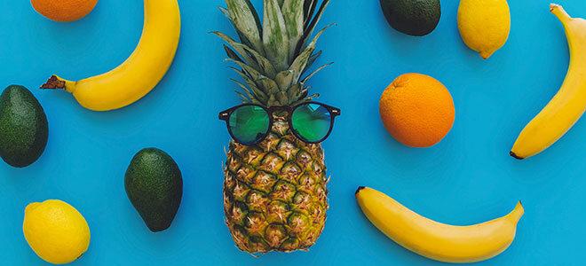Mehrere Südfrüchte wie Bananen, Orangen und Ananas. Sie sollten nicht im Kühlschrank gelagert werden.