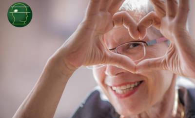 Eine Parkinsonpatientin formt mit ihren Händen ein Herz und lächelt hindurch. Sie hat sich erfolgreich mit der Therapie der ewigen Nadel behandeln lassen und Lebensqualität zurückgewonnen.