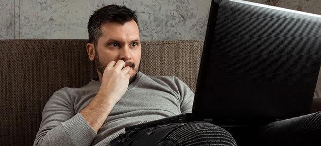 Ein Mann Mitte 30 sitzt auf dem Sofa und schaut gebannt auf seinen Laptop. Er sieht einen Sexfilm, weil er pornosüchtig ist.