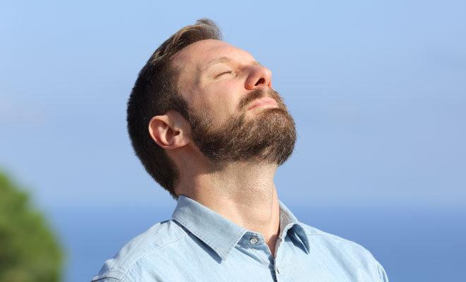 Ein Mann mittleren Alters atmet tief durch und wirkt entspannt.