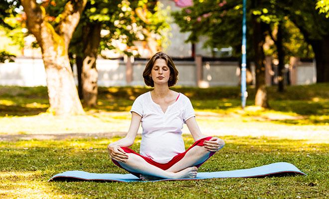 Eine schwangere Frau meditiert im Park. Schwangerschaftsübungen wie diese sind sehr gesund.