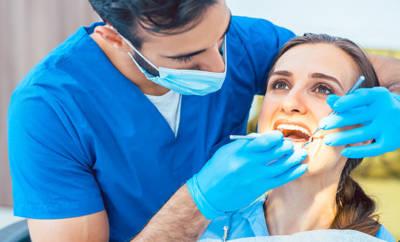 Ein Zahnarzt führt bei einer Patientin eine professionelle Zahnreinigung durch.