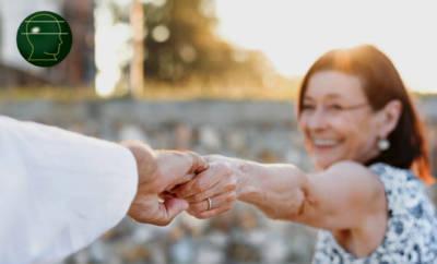 """Eine Senioren hält sich fröhlich an der Hand ihres Partners fest. Sie hat durch die Parkinson-Therapie der """"ewigen Nadel"""" Lebensqualität zurückgewonnen."""
