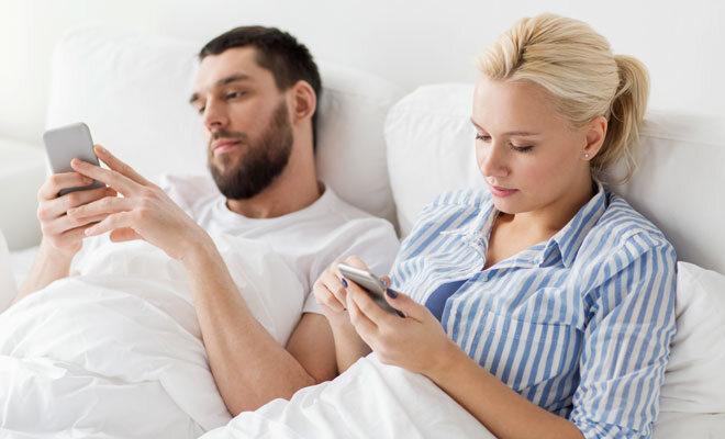 Ein junges Ehepaar liegt im Bett. Beide Partner sind mit ihrem Smartphone beschäftigt.