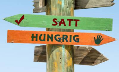 """Zwei Schilder: Auf einem steht das Wort """"satt"""", auf dem anderen das Wort """"hungrig"""". Nicht immer müssen Sie während der Fastenzeit auf Essen verzichten. Wir haben 5 Alternativen zum Lebensmittelfasten für Sie zusammengestellt."""