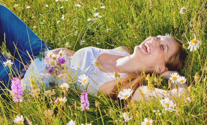 Eine junge Frau mit Heuschnupfen liegt beschwerdefrei in einer Sommerblumenwiese.