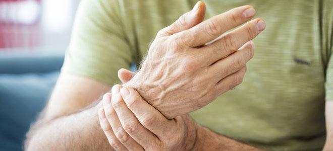 Ein Mann mit dem Sjögren-Syndrom hält seine rechte Hand, die durchblutungsgestört ist.