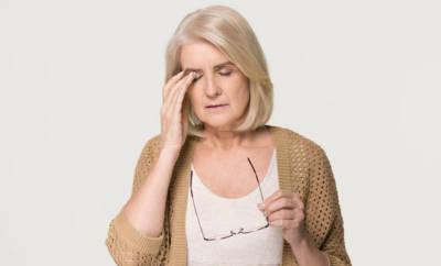 Eine Seniorin reibt an ihren trockenen Augen. Sie leidet am Sjögren-Syndrom.