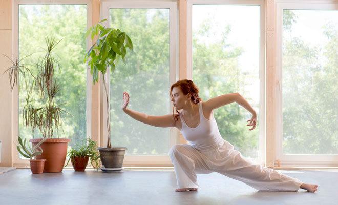 Eine junge Frau praktiziert Tai Chi in ihrem hellen Wohnzimmer.