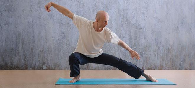 Ein Mann um die 60 übt Tai Chi auf einer Matte.
