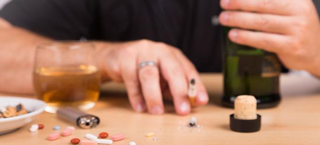Ein Mann, der raucht, trinkt und Tabletten nimmt. Solch ein Drogenmissbrauch kann zu einem Delirium führen.