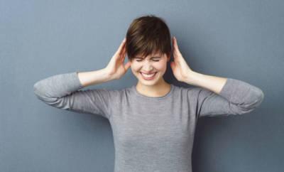 Eine junge Frau drückt ihre Augen Zu und hält sich die Hände an die Ohren. Sie ist hochsensiblel.